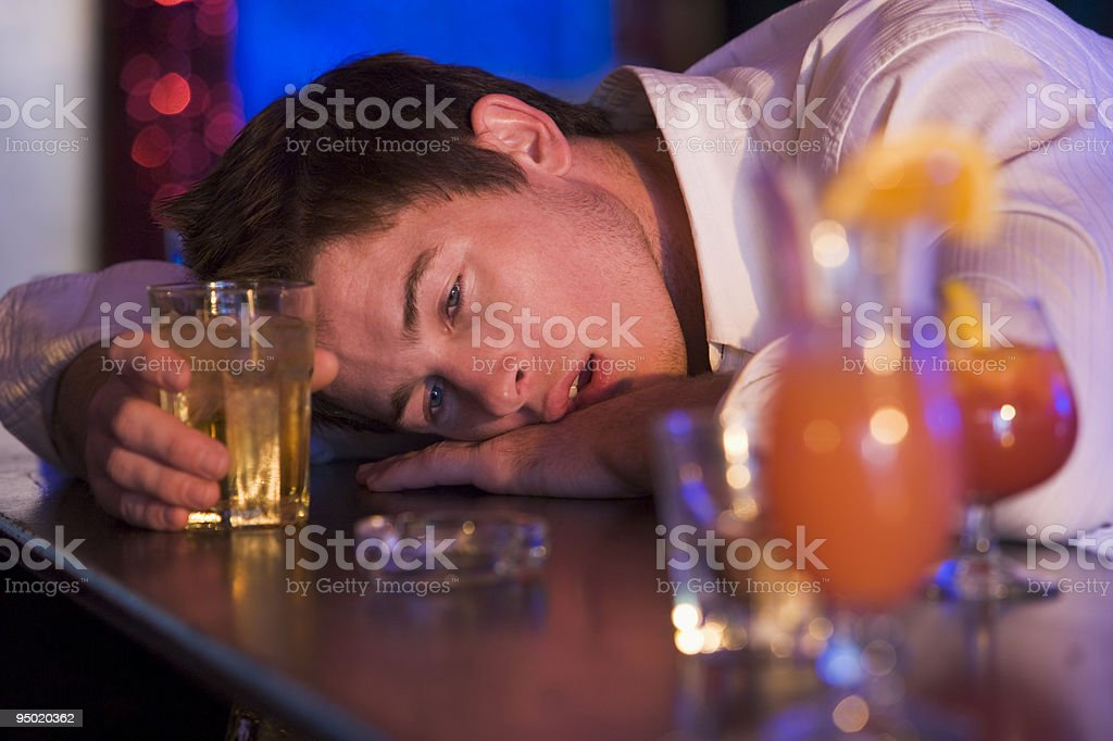 Drunk young man resting head on bar counter stock photo