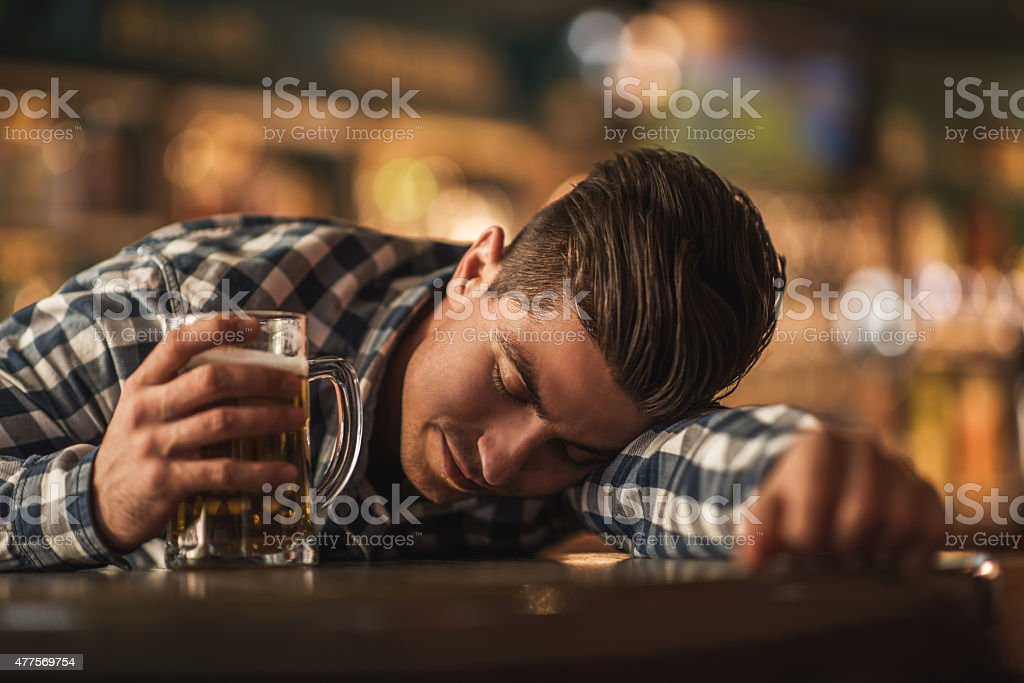Drunk young man sleeping in a bar. stock photo