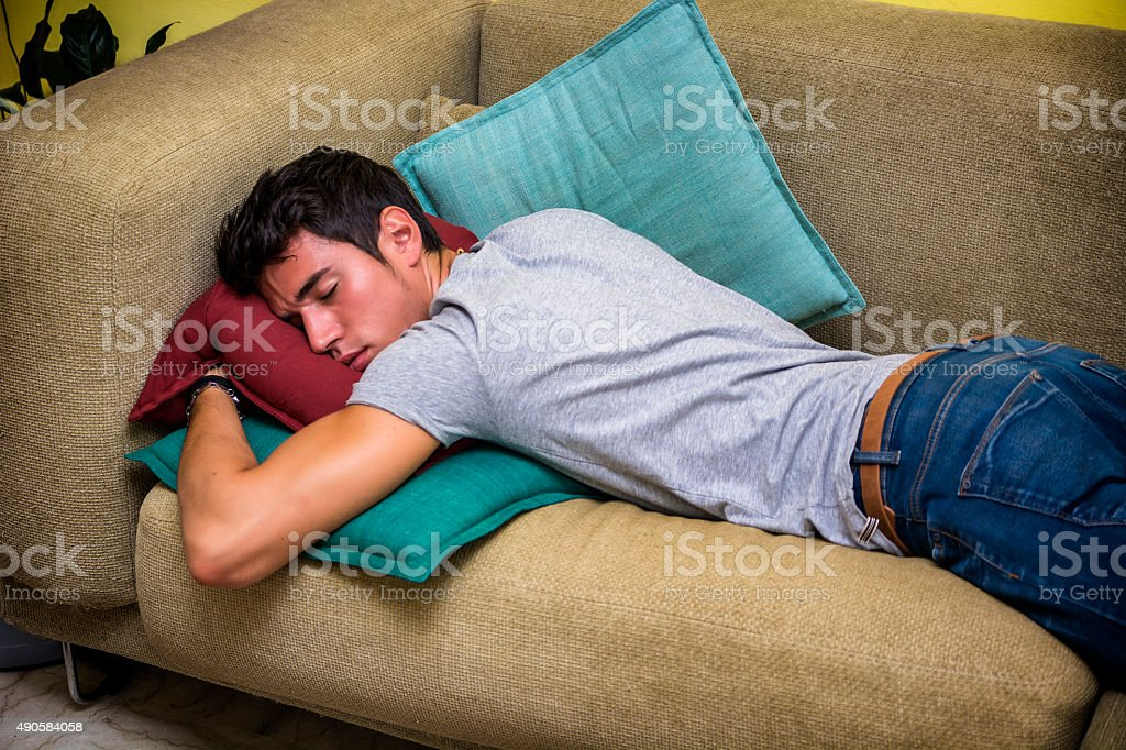 Drunk Young Man Sleeping on the Living Room Couch stock photo