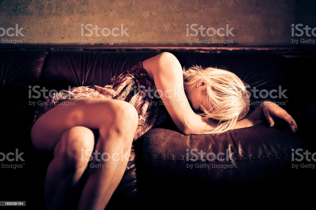 Drunk young woman lying on the sofa stock photo