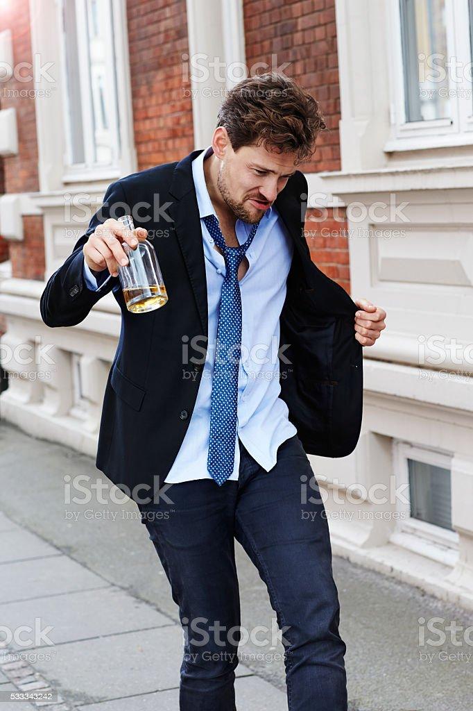 Drunken businessman walking with bottle stock photo