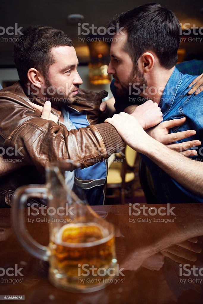 Drunken male quarrel in bar stock photo