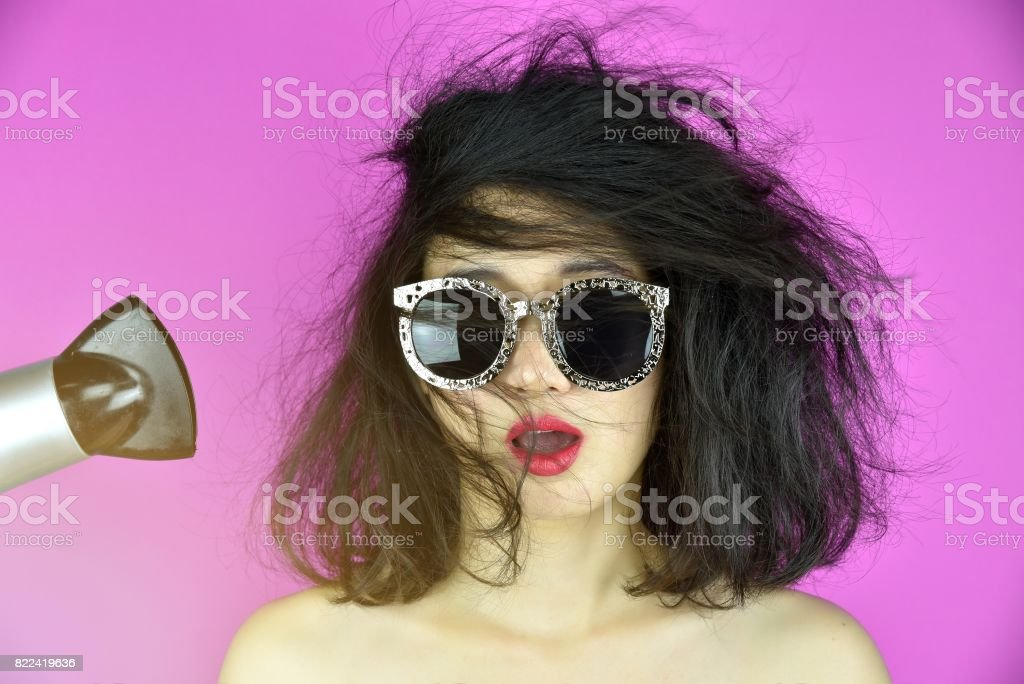 Dry and damaged hair, Hair loss problems cause by heat hair styling tools hair dryer, Funny girl and bad hair day. Selective Focus stock photo