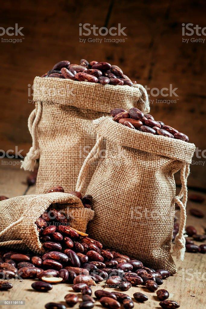 Dry beans in burlap sacks stock photo