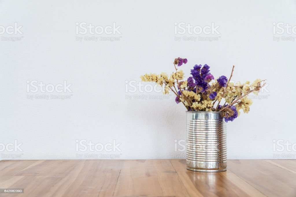 Dry colorful flowers in metal can decorative on wood table stock photo