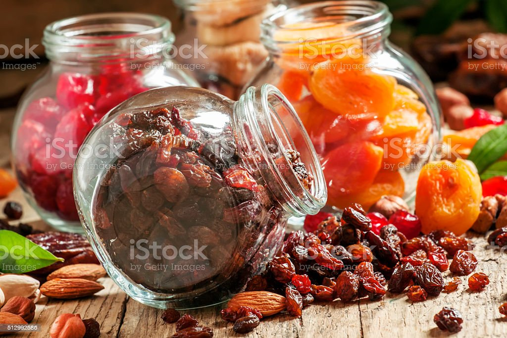Dry dark raisins in a glass jar, assorted dried fruit stock photo