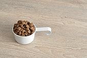 Dry dog food in a white mug