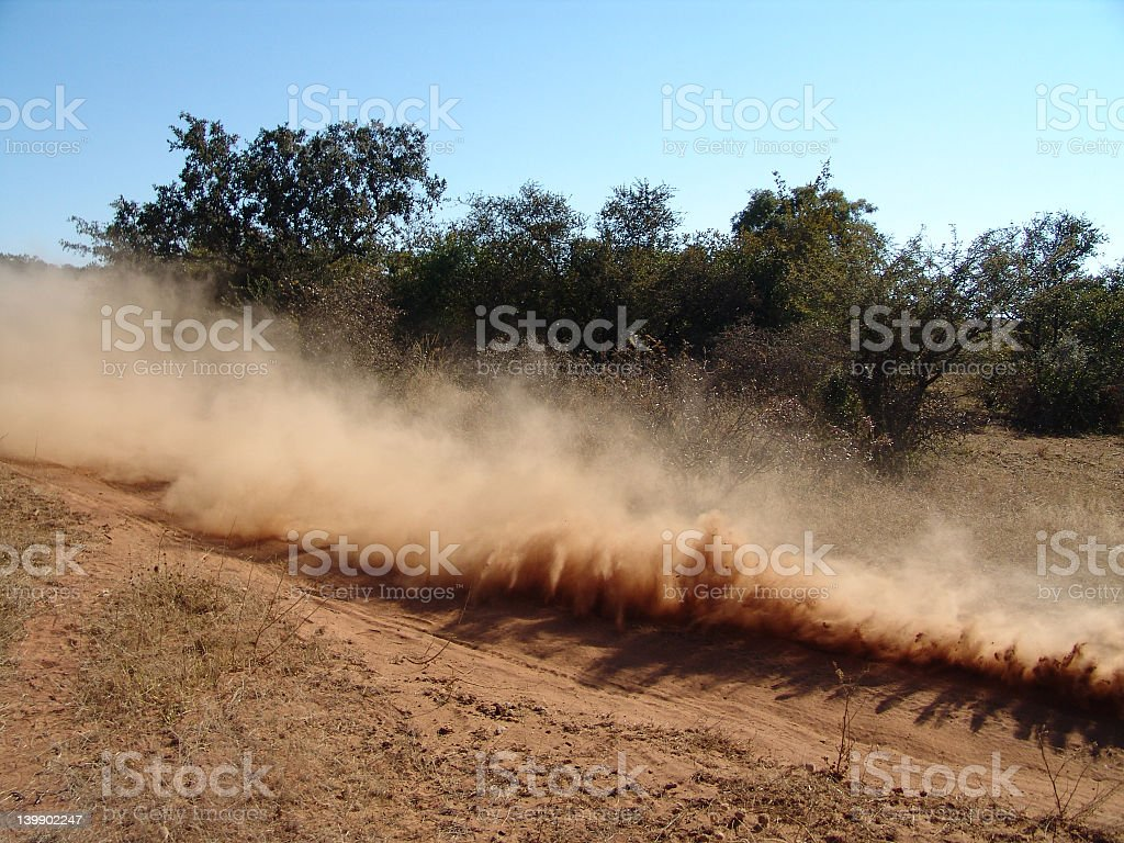 Dry field with dust cloud and trees in background stock photo