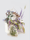 dry flowers in white basket and two handmade linen sacks