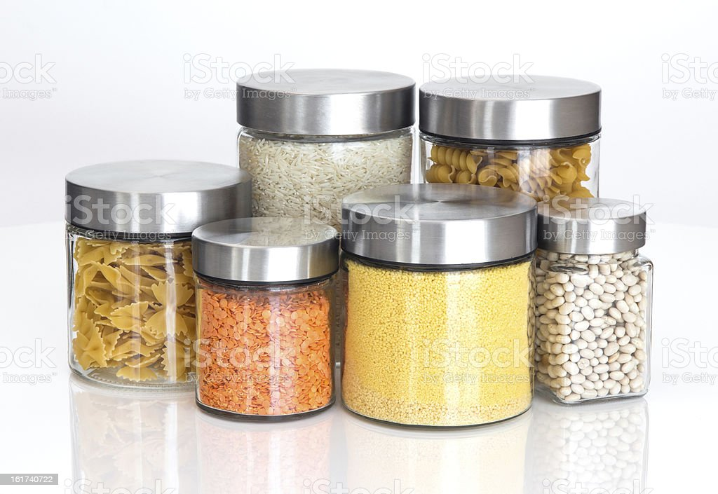 Dry food ingredients in varying sized glass jars on white stock photo
