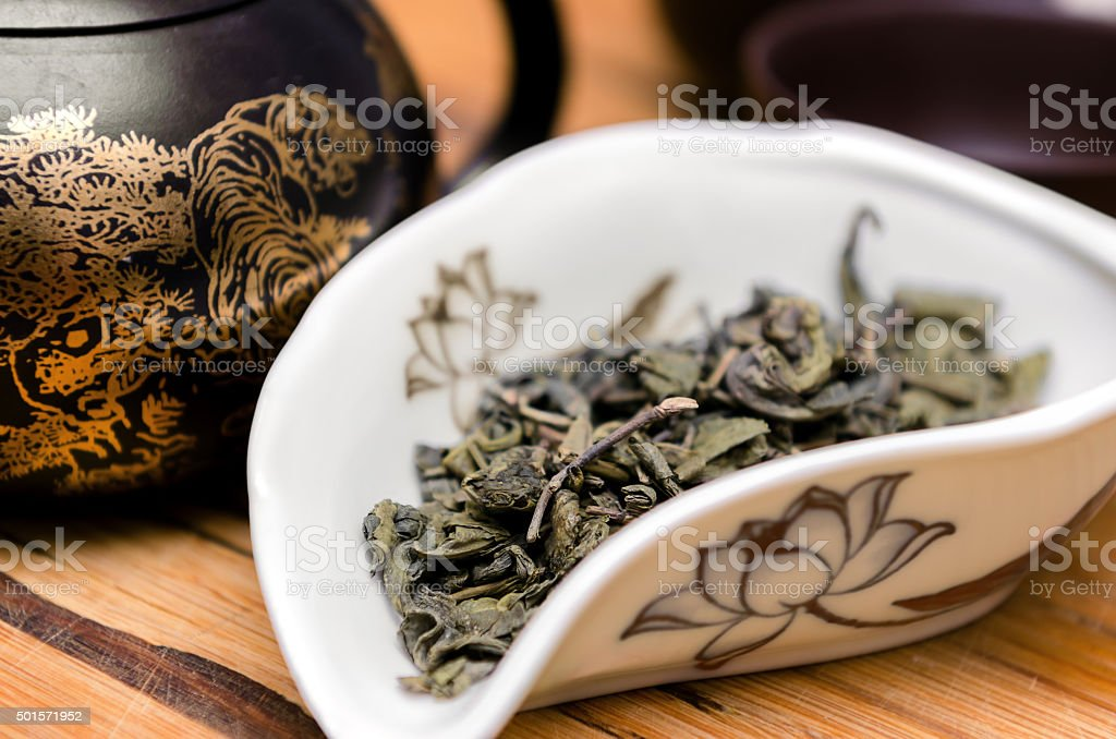 Dry green tea on wooden background stock photo