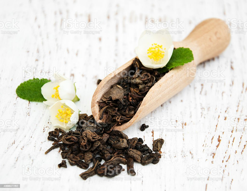 Dry green tea with jasmine flowers stock photo