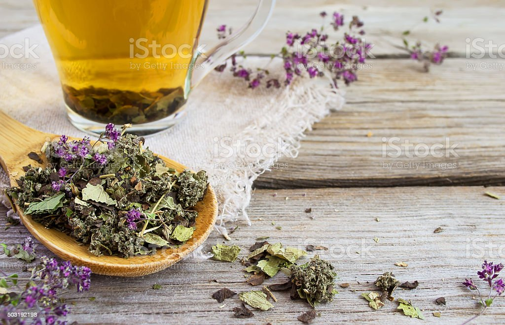 Dry herb tea on a background of cups with tea stock photo