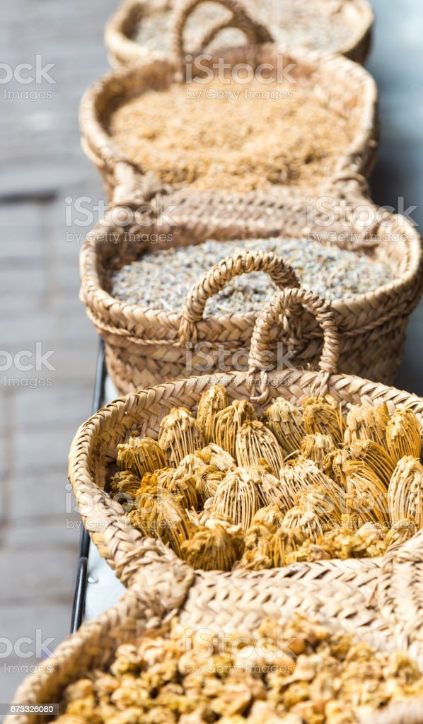 Dry herbs in handmade braided basket in traditional Arabic farmacy stall stock photo