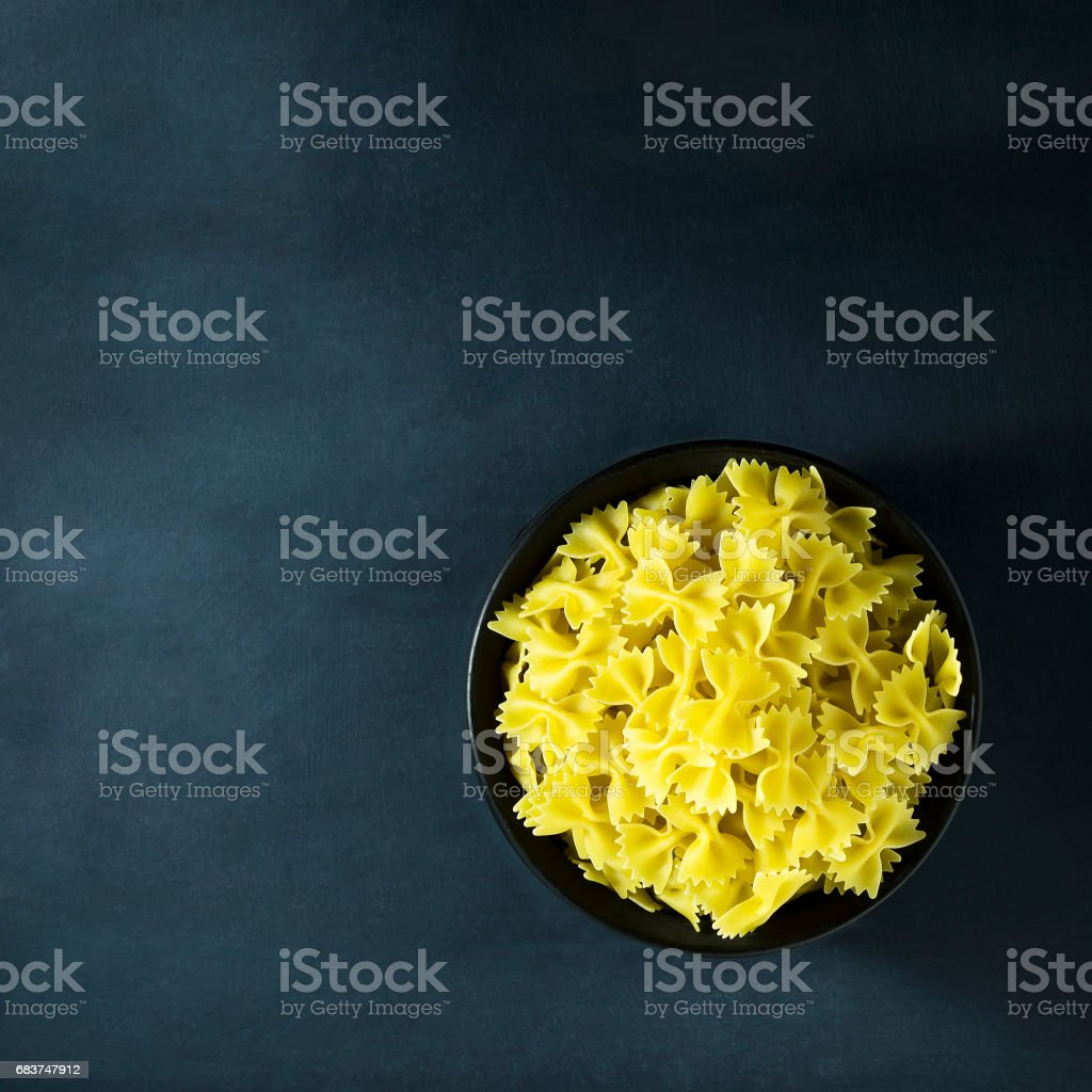 Dry Italian pasta in a bowl on a dark blue background. stock photo