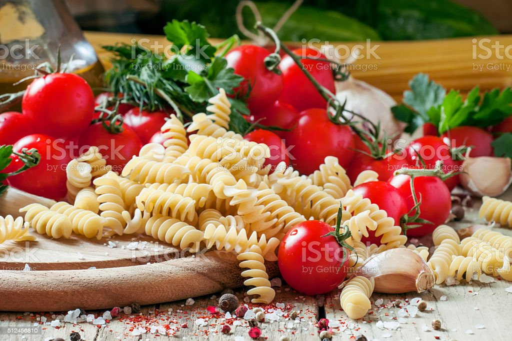 Dry Italian pasta spiraline with cherry tomatoes, parsley stock photo