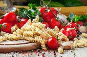 Dry Italian pasta spiraline with cherry tomatoes, parsley