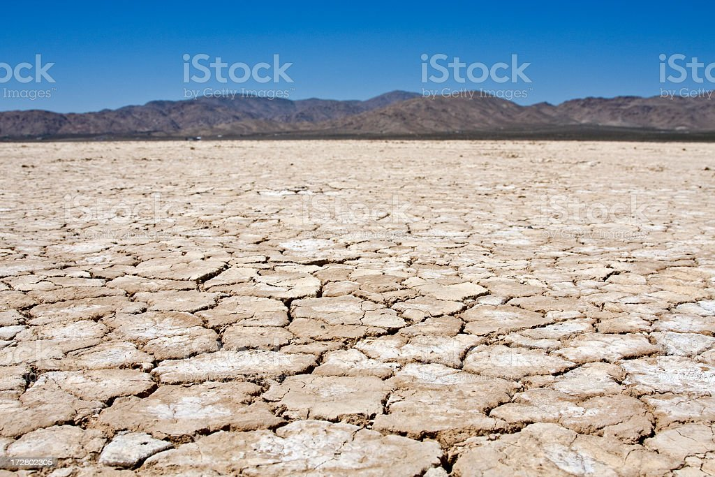 A dry lakebed landscape in front of mountains under blue sky stock photo