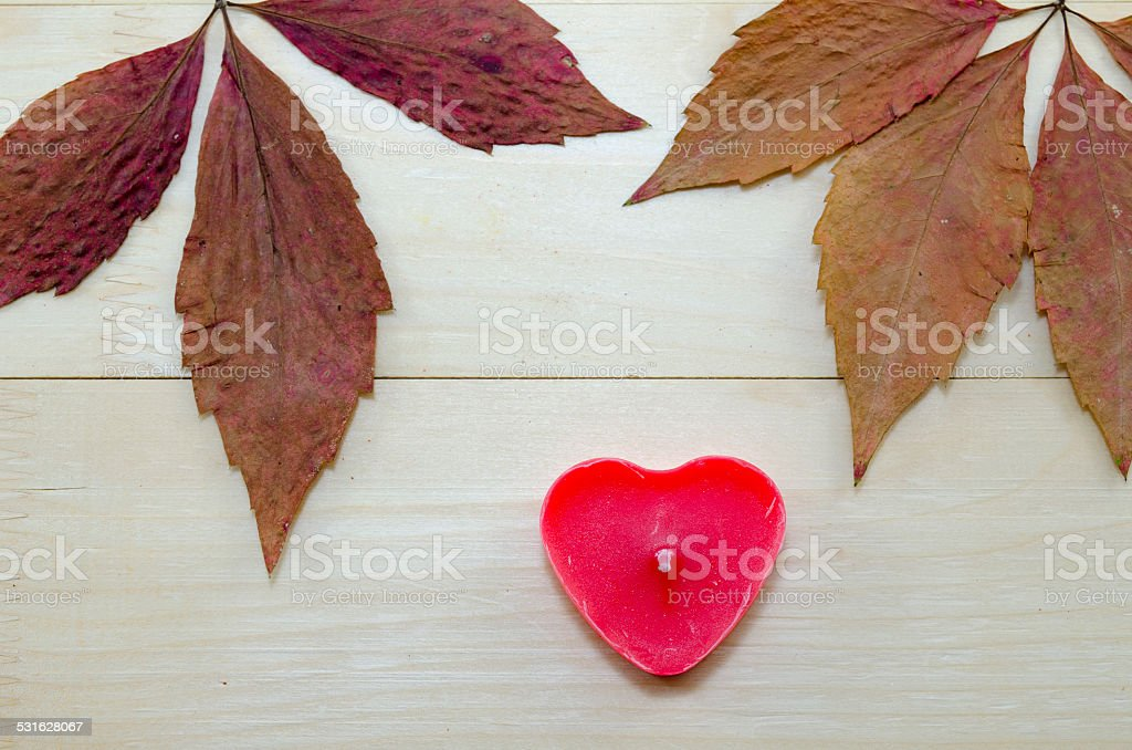 Dry leaves and a red heart shaped candle royalty-free stock photo
