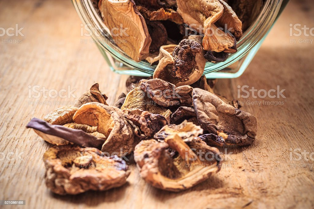 Dry mushrooms in jar on wooden table. stock photo
