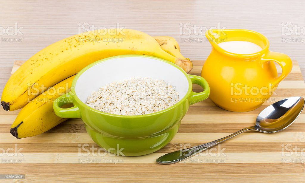 Dry oat flakes in green bowl, milk jug, bananas stock photo