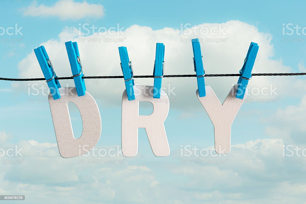 Dry on clothes line with blue pegs and white letters stock photo