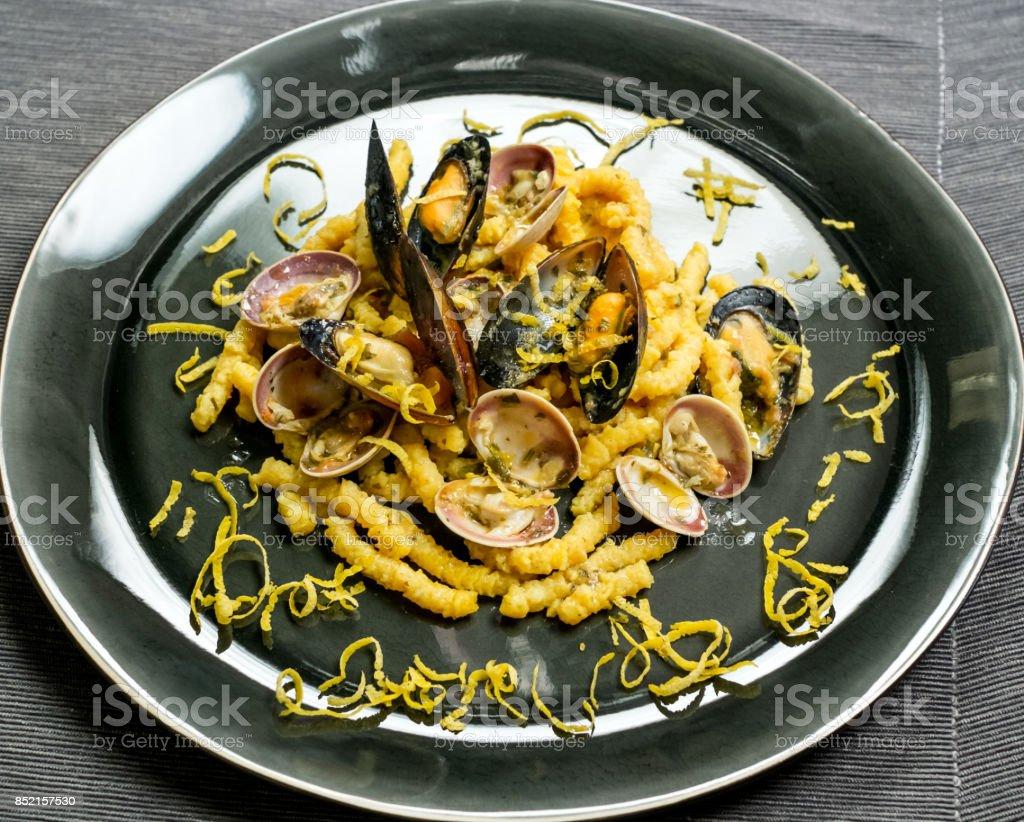 dry passatelli with shellfish and lemon bark strips stock photo
