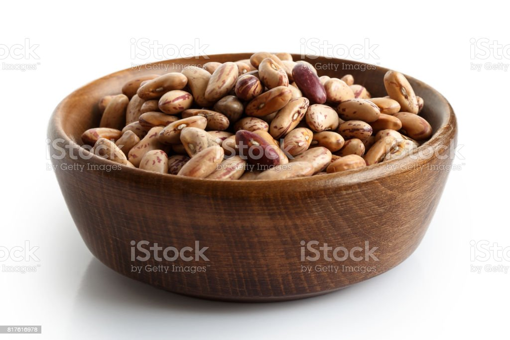 Dry pinto beans in dark wooden bowl isolated on white. stock photo