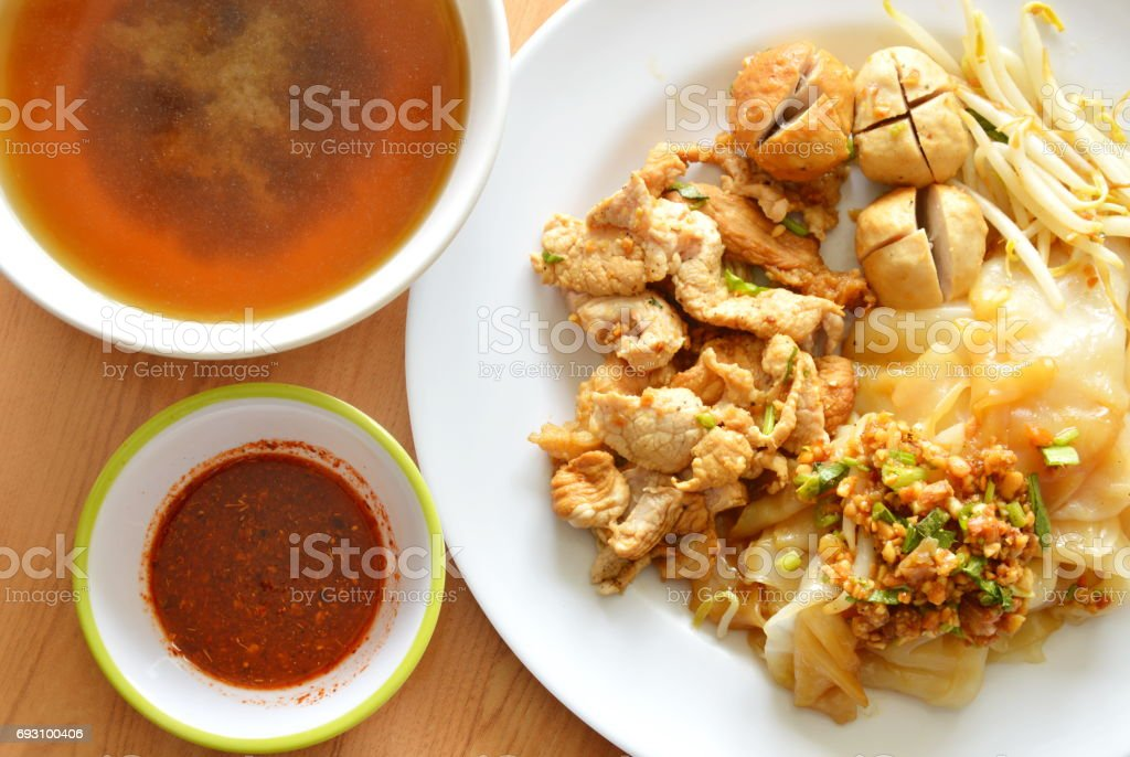 dry rice noodle  topping pork ball and soup stock photo