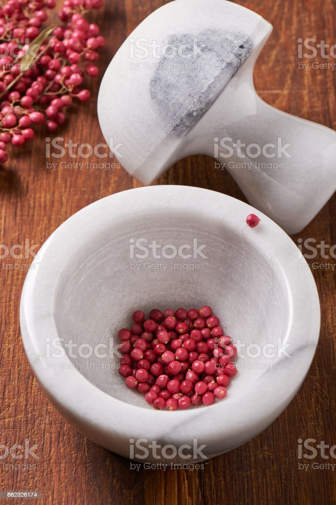 Dry rose pepper in white marble mortar next pestle stock photo