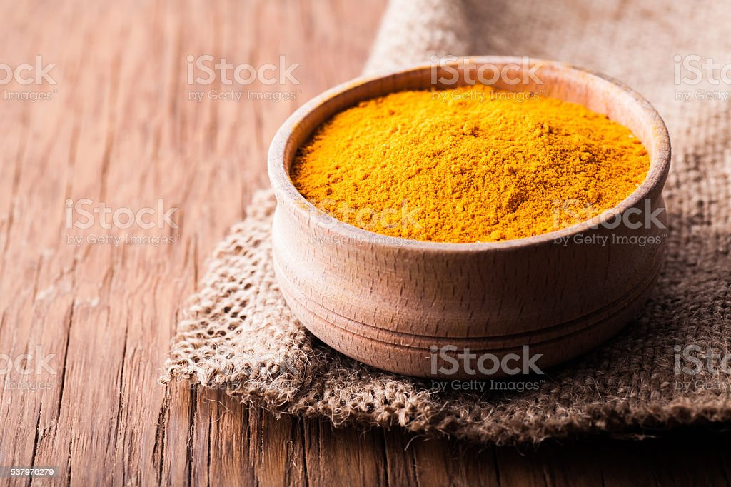 dry spice turmeric in a wooden bowl close-up stock photo
