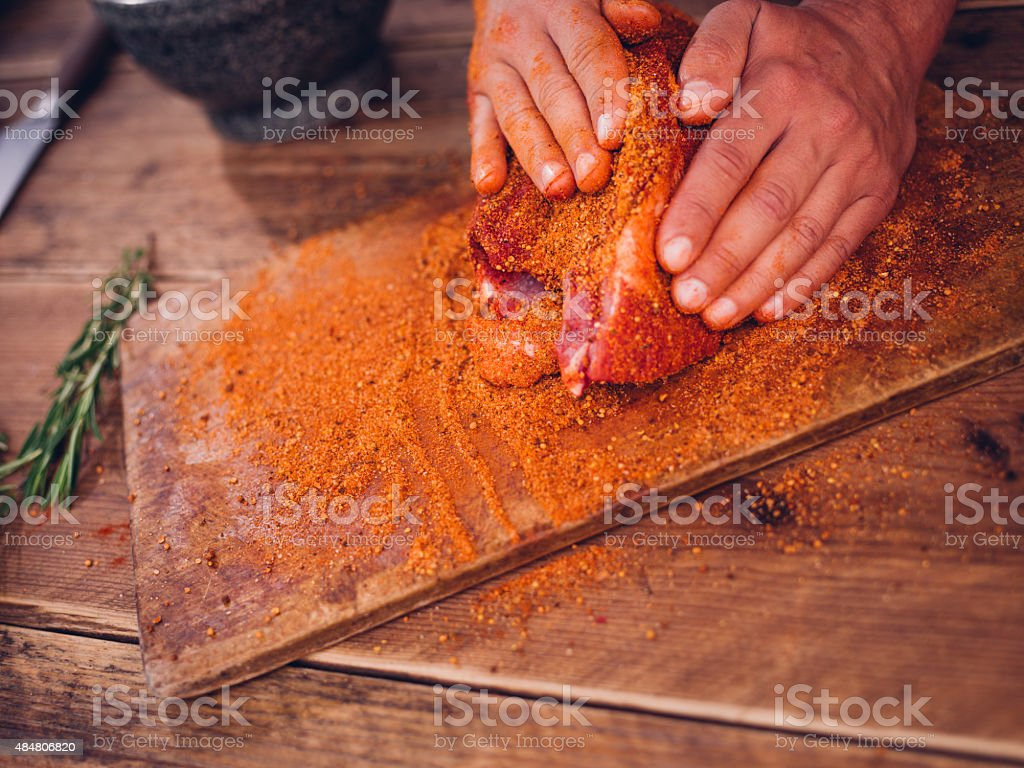 Dry spicy seasoning being rubbed into raw pork stock photo