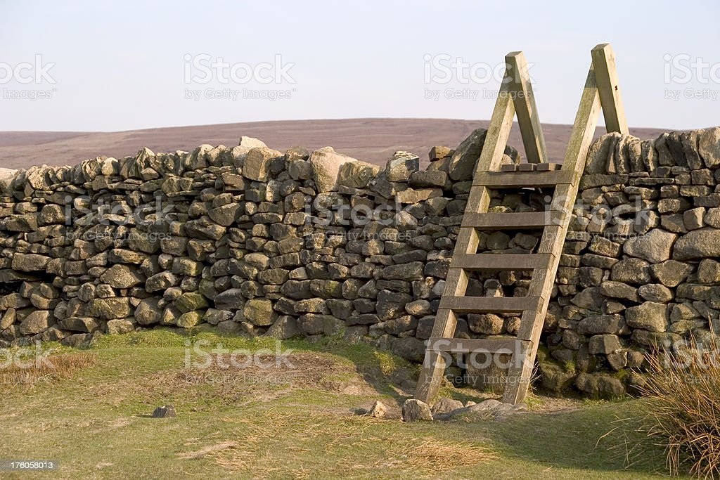Dry stone wall with a traditional ladder stile stock photo