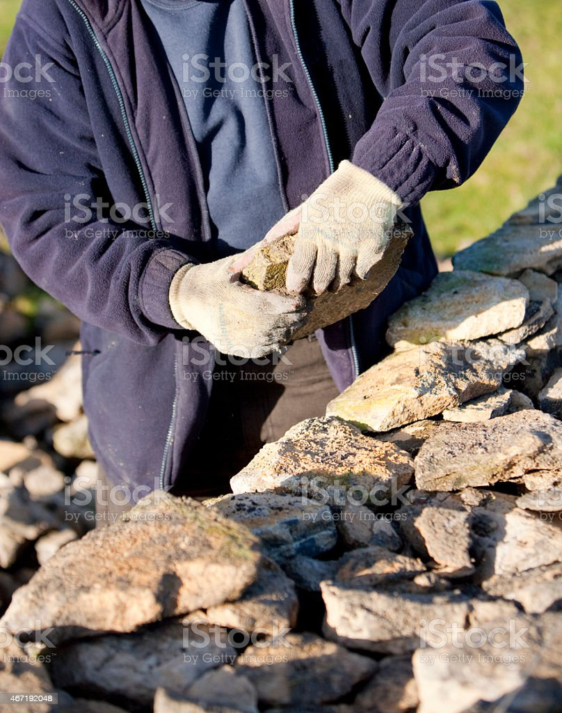Dry stone waller repairing a boundary wall stock photo