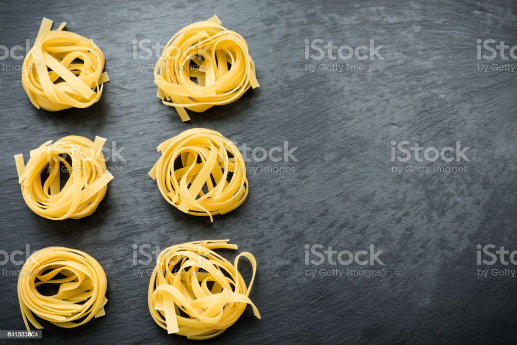 Dry tagliatelle on gray table stock photo