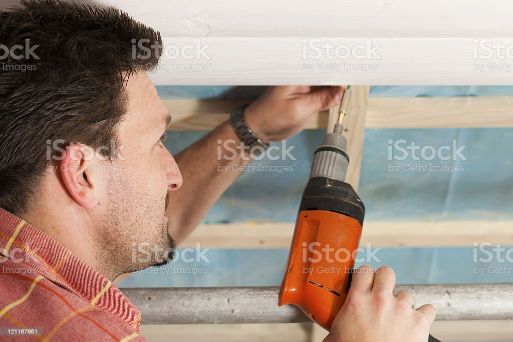 Dry waller with cordless screwdriver stock photo