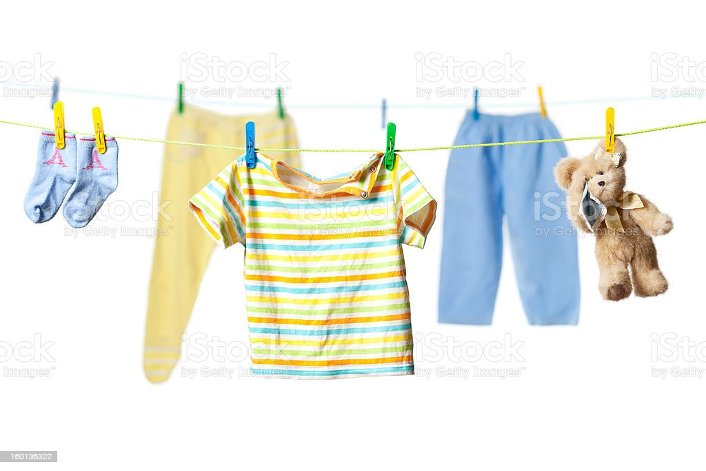 Drying baby clothes and a teddy bear stock photo