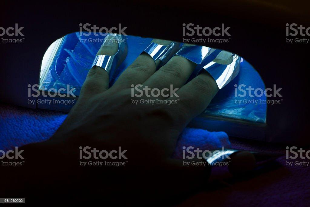 Drying female fingernail wax polish in ultraviolet light dryer stock photo