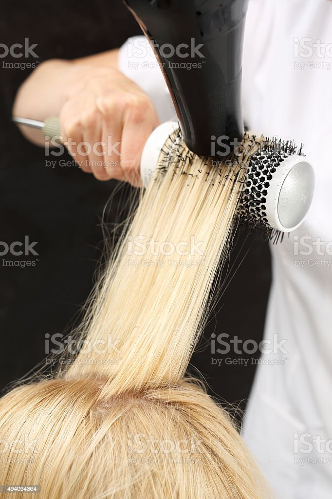 Drying hair on a round brush stock photo