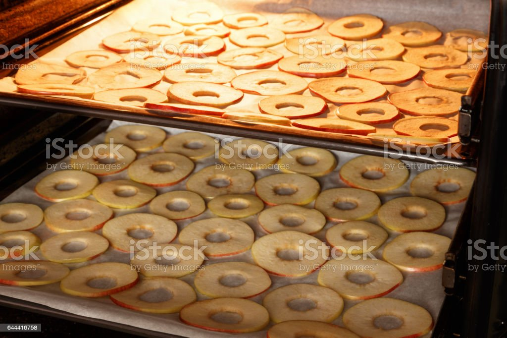 drying slices of apples at home on the baking sheets stock photo