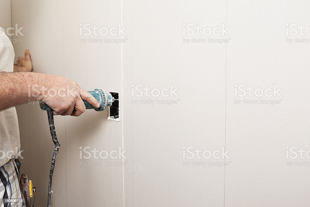 Drywall Installer Using Rotary Saw to Cut Outlet Hole stock photo