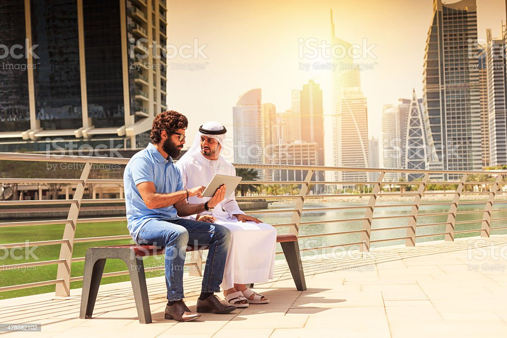 Dubai - Young mens using digital tablet in the city stock photo