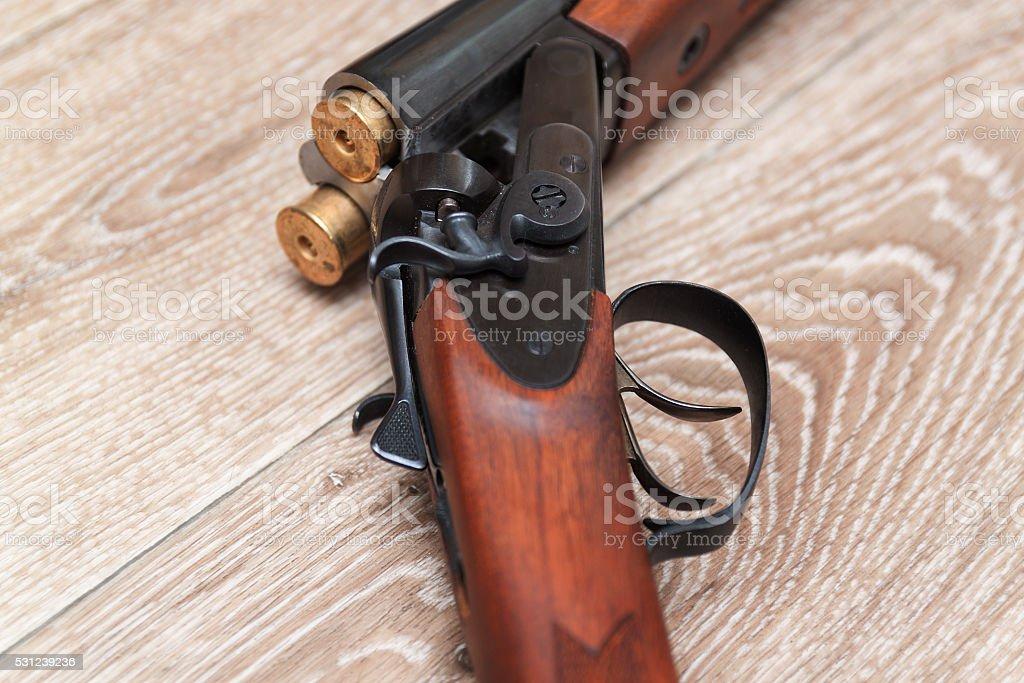 dubbelbarreled shotgun with bullets on wooden stock photo