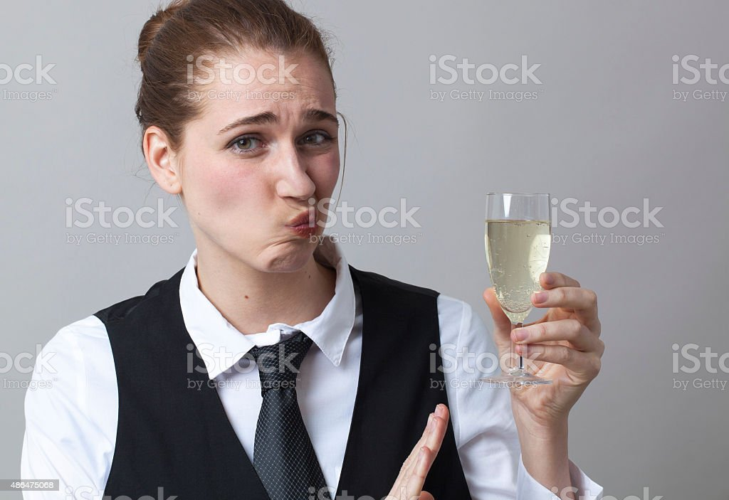 Dubious 20s girl resisting in drinking more Champagne at party stock photo