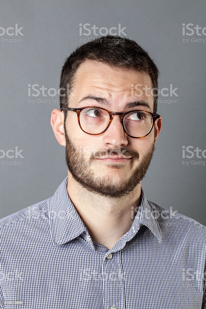 dubious 20s male manager with beard and eyeglasses having ideas stock photo