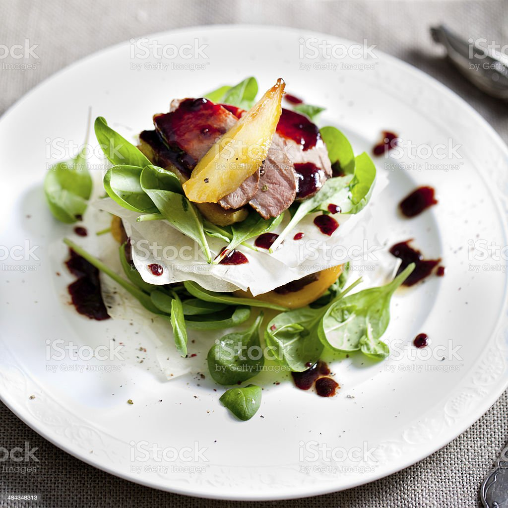 Duck breast roasted with pear, salad on a white plate stock photo