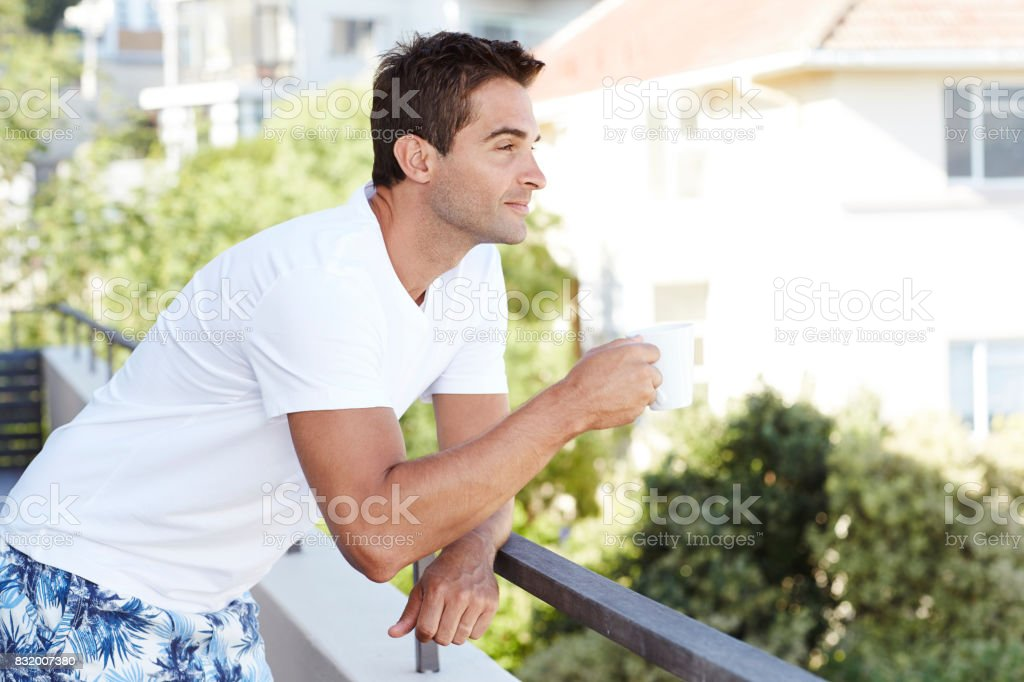 Dude with coffee on balcony stock photo