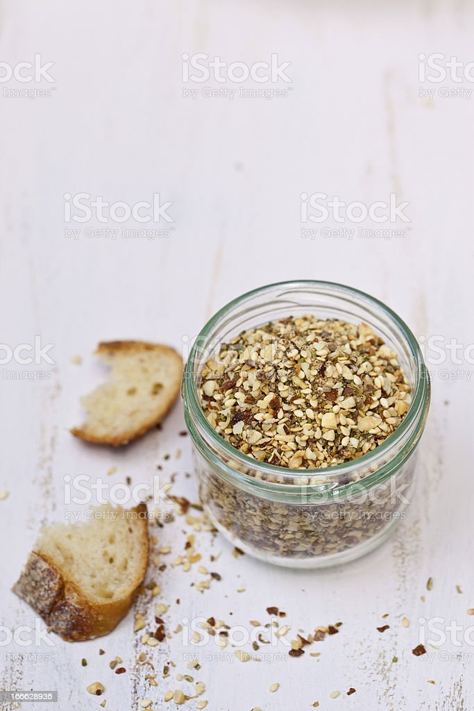 Dukkah in the glass with crusted bread. royalty-free stock photo