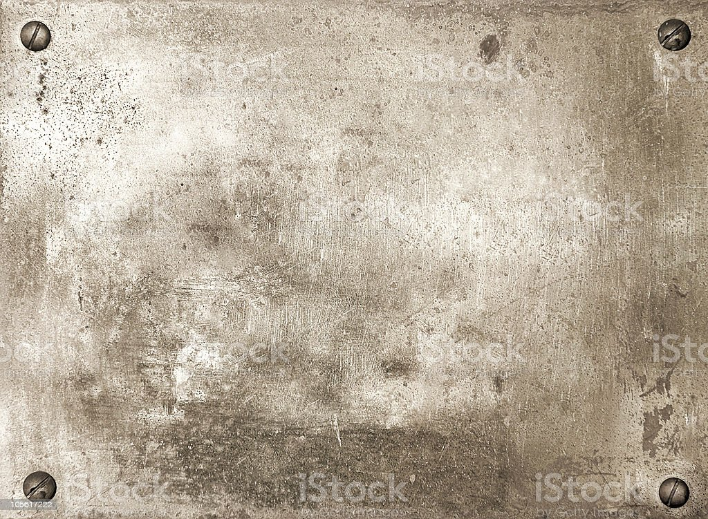 A dull brass metal plate with scratch and four screws stock photo