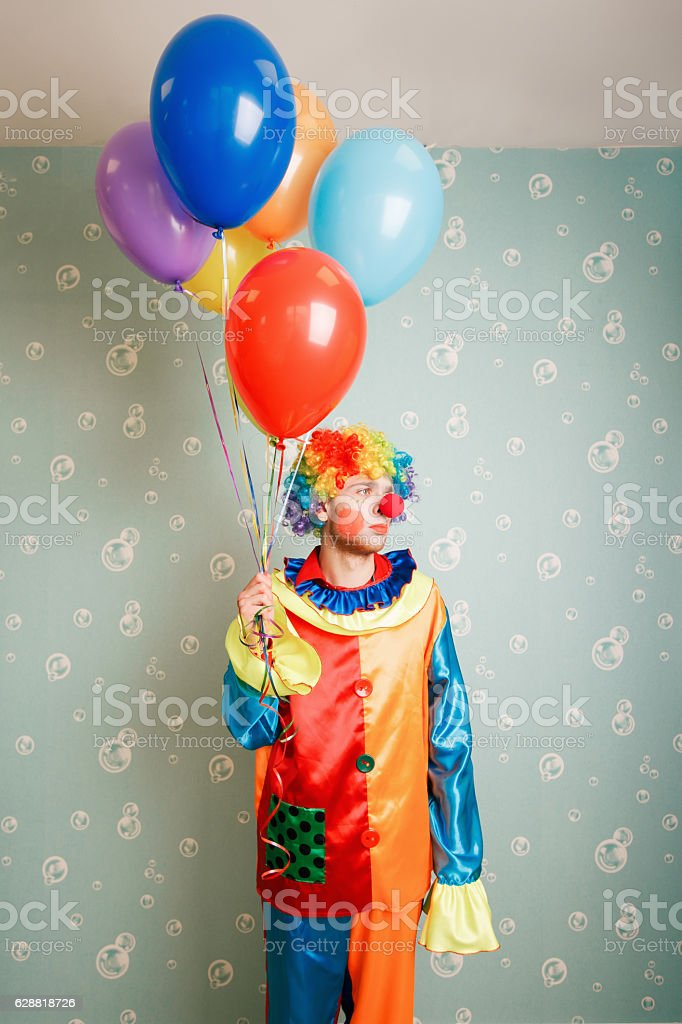 Dull clown with a bunch of balloons. stock photo
